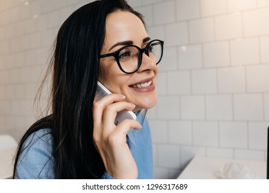happy busy business woman wearing glasses talking on the phone about business