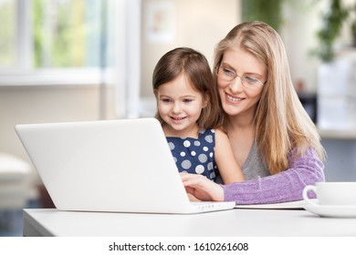 Happy busy mother working with a child on laptop