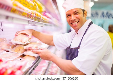 happy butcher organizing meat products in supermarket