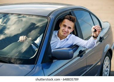 Happy buyer holding car keys inside his new vehicle