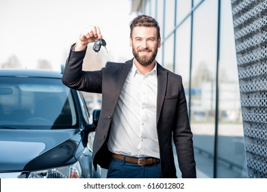 Happy buyer holding keys near the car in front of the modern avtosalon building