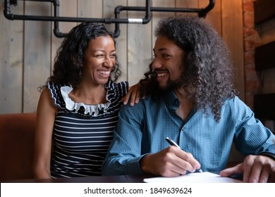 Happy buyers. Excited smiling mixed race married couple sitting at table in cozy cafe having business meeting with lawyer agent advisor signing paper contract, accepting inheritance, purchasing estate