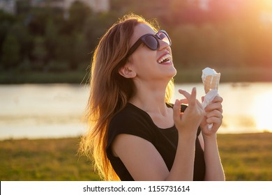 happy californian beautiful woman in sunflasses eat ice cream in a waffle horn cone at sunset on the beach. cool photosession photoshoot of girl on summer park