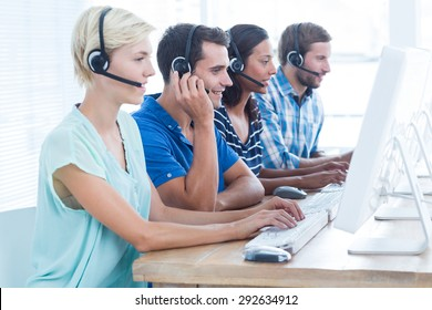 Happy call centre workers on their laptops