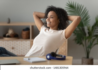 Happy calm african American millennial girl sit lean back in chair hands over head look in distance dreaming visualizing, smiling black young woman relax at workplace take pause distracted from work