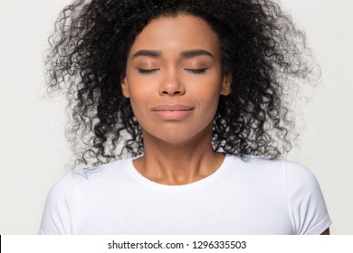 Happy calm african woman with beautiful face take deep breath of fresh air, grateful mindful black lady enjoy inhaling meditating feel no stress free harmony isolated on white grey studio background