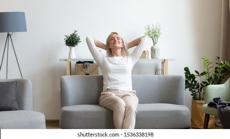 Happy calm middle aged old woman resting on sofa with eyes closed breathing fresh air hold hands behind head relaxing at home, healthy smiling mature lady enjoying no stress in living room concept