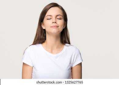 Happy calm teen girl enjoying good smell or pleasant fragrance, serene mindful young woman taking deep breath feel no stress free inhaling fresh air relaxing isolated on white grey studio background