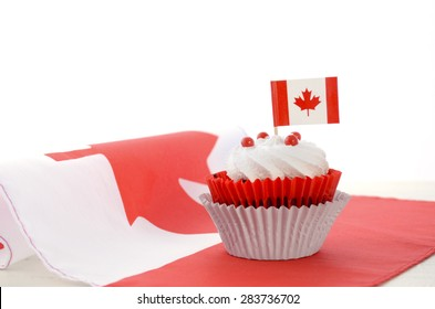 Happy Canada Day celebration cupcake with red and white Canadian maple leaf flag on white wood table.