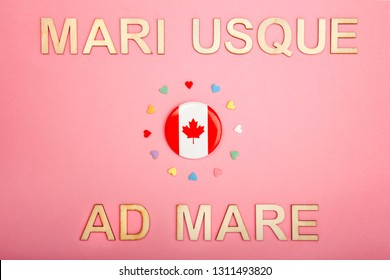 Happy Canada Day greeting card with wooden letters. Canadian latin motto slogan saying from sea to sea and flag with many hearts on living coral pink background. Multiculturalism concept
