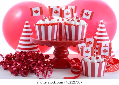 Happy Canada Day Party Cupcakes on a red cake stand with maple leaf flags on a white wood table with party balloons, hats and decorations.