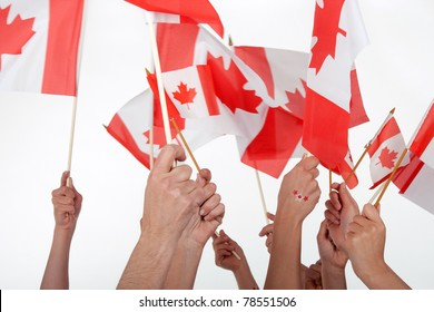 Happy Canada Day! Raised hands waving Canadian flags.
