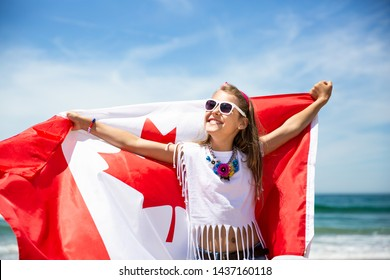 Happy Canadian girl carries fluttering white red flag of Canada against blue sky and ocean background. Canadian flag is a symbol of freedom, liberty, democracy, independence. Canada Day