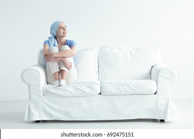 Happy cancer patient feeling relieved and holding her knees on a white sofa