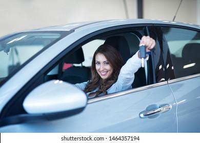 Happy car buyer sitting in new vehicle showing keys in dealership showroom.