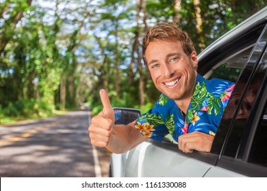 Happy car driver man driving safe on road trip travel doing thumbs up in satisfaction of cars rental. Smiling young male model.