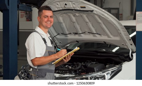 Happy car mechanic smiling to the camera while filling papers