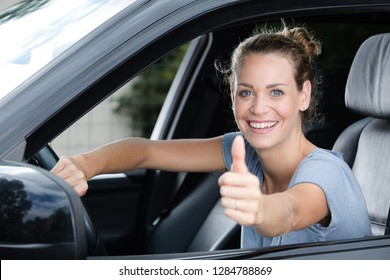 happy car owner looking at camera showing thumbs up
