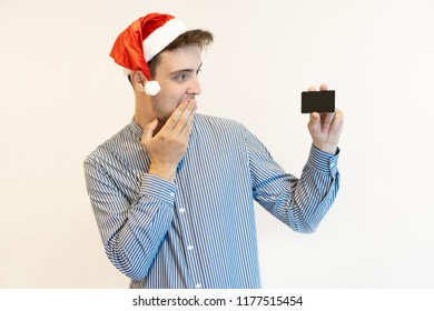 Happy cardholder looking forward to Christmas shopping. Handsome young man in Santa hat covering mouth with hand and showing credit card at camera. Christmas purchases concept