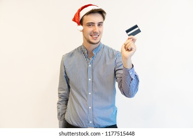 Happy cardholder ready for Christmas shopping. Handsome young man in Santa cap advertising credit card. Banking and special offers concept