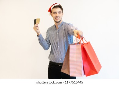 Happy cardholder recommending Christmas shopping. Handsome young man in Santa hat holding credit cards and giving shopping bags at camera. Christmas sale concept
