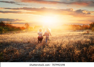 Happy and carefree life - two friends run to the sun