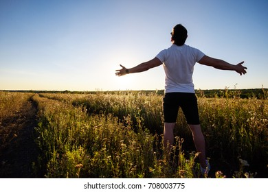 Happy and carefree man standing on a country road close to the wild steppe field. Freedom and love to nature concept. Male adult observes the sunset with optimism and confidence.