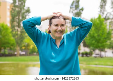 Happy carefree middle aged woman relaxing in park. Excited smiling plus sized lady keeping clasped hands on head and looking away. Woman in park concept