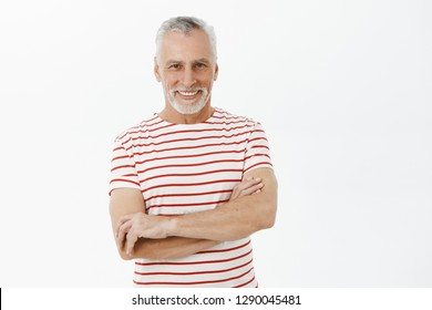 Happy and carefree retired senior man with white beard and hair in fancy striped t-shirt holding hands crossed against chest in self-assured gesture smiling pleased and assured at camera