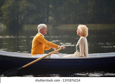 Happy carefree senior couple riding boat on lake and talking, handsome elderly man rowing oars
