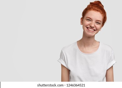 Happy carefree smiling freckled girl tilts head, has toothy smile, freckled skin, dressed in casual clothes, models against white background with copy space for your advertisement or promotional text