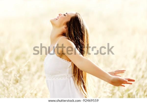 自然と温かい夏の日を手を伸ばして、ハッピーケアフリーの活力の自由な少女