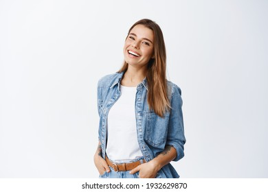 Happy carefree woman with joyful expression, smiling while standing in relaxed pose against white background, holding hands in jeans pockets
