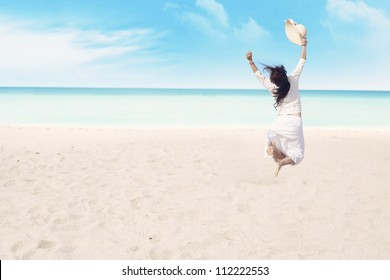Happy carefree woman jumping on beach celebrating her freedom
