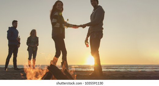 Happy Carefree Young Friends Having Fun And Drinking Beer By Bonefire On The Beach As The Sun Begins To Set
