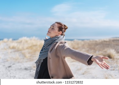 Happy carefree young woman on a winter beach enjoying the warm sunshine with outspread arms and closed eyes