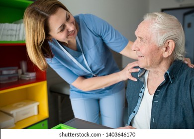 Happy caretaker assisting senior man. Friendly nurse supporting old man with Parkinson's Disease
