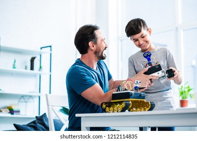 Happy caring father and his son holding robotic devices while working on engineering project together
