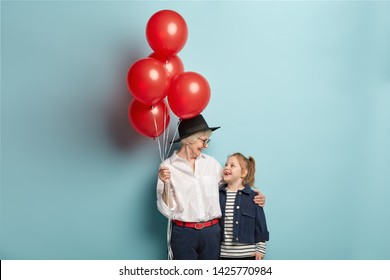 Happy caring grandmother holds bunch of red air balloons, congratulates granddaughter with birthday, organize holiday, wear festive clothes, isolated over blue background. Grandmom embraces kid