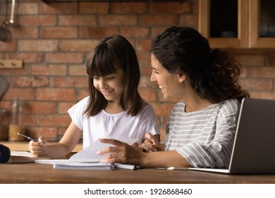 Happy caring young Latino mom do home work learn distant use computer with small biracial daughter. Smiling Hispanic mother help girl child with home task preparation. Online education concept.