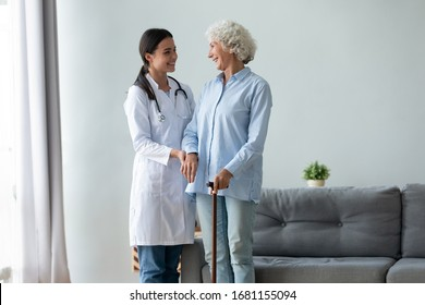 Happy caring young woman doctor or nurse and positive old lady with walking stick stand hugging talking, attentive caregiver support comfort optimistic senior grandmother give help and assistance