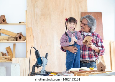Happy carpenter family. The little girl and his father smiled happily while working on woodwork in a wooden shop.