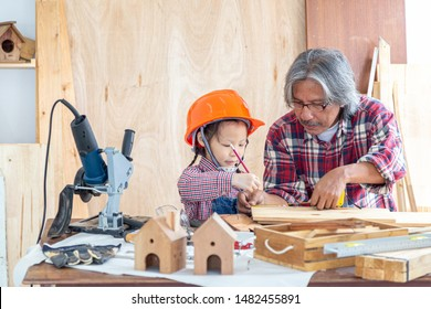 Happy carpenter family. The little girl and her grandfather smiled happily while working on woodwork in a wooden shop.