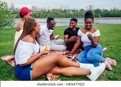 happy casual america african people having fun and eating burger outdoors lifestyle,students for a break summer evening cloudy weather in park