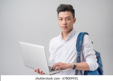 Happy casual asian male student using laptop isolated on a gray background