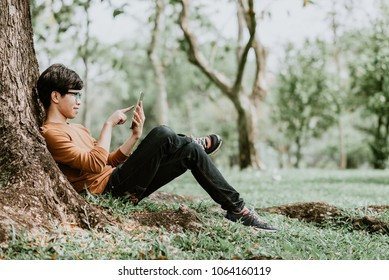 Happy casual Asian man using a smart phone outdoor sitting under tree in park