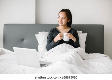 Happy casual beautiful Asia woman working on a laptop sitting on the bed in the house.
