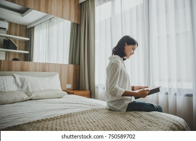 Happy casual beautiful woman reading a book sitting on the bed in the house.