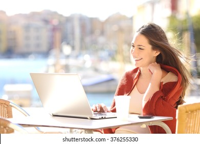 Happy casual beautiful woman watching videos or enjoying entertainment content in a laptop sitting in a coffee shop terrace outdoors in a sunny day