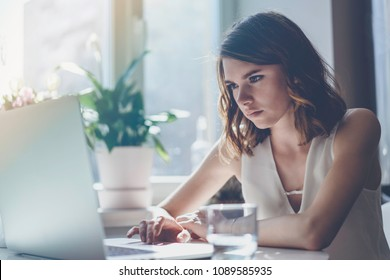 Happy casual beautiful woman working on a laptop sitting at the table in living room of modern house. Film effect